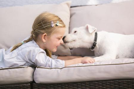 Foto de Young girl lying with pet dog on couch - Imagen libre de derechos