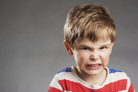 Photo for Young boy looking angry, clenching teeth against gray background - Royalty Free Image