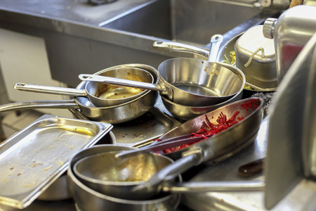 Photo for Kitchen in restaurant, sink filled with dirty metal dishes - Royalty Free Image