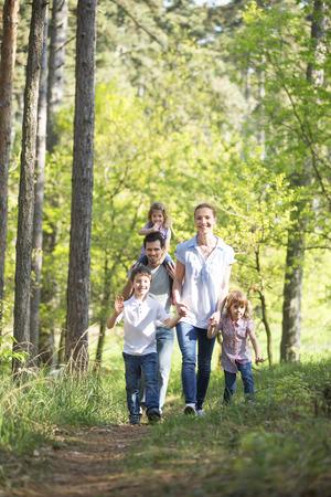 Photo pour happy family taking a walk in forest - image libre de droit