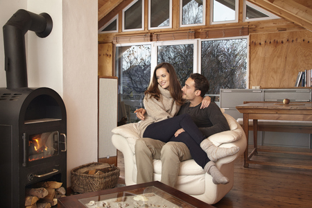 Photo for Couple sitting by fireplace - Royalty Free Image