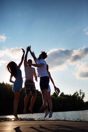Foto de Group of friends jumping on jetty giving high five - Imagen libre de derechos
