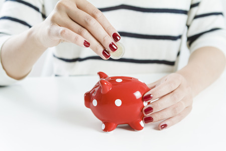 Photo pour Woman saving money with red piggy bank - image libre de droit