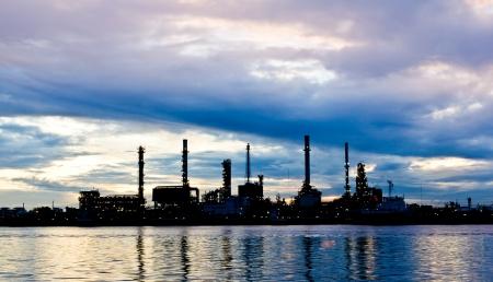 Photo pour Silhouette Oil refinery plant at morning along river in Bangkok - image libre de droit