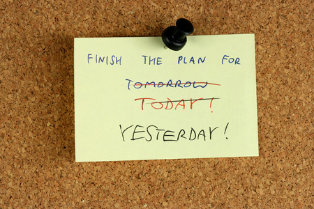 Yellow small sticky note on an office cork bulletin board. Deadline meeting failure.