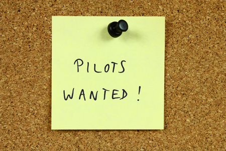 Yellow sticky note pinned to an office notice board. Pilots wanted - airline employment and aviation career recruitment message.