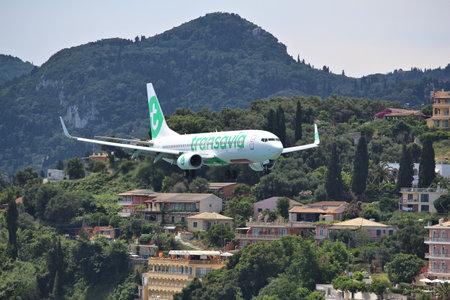 Foto de CORFU, GREECE - JUNE 5, 2016: Transavia Boeing 737-800 arrives at Corfu International Airport, Greece. Transavia is a Dutch low-cost airline owned by KLM. - Imagen libre de derechos