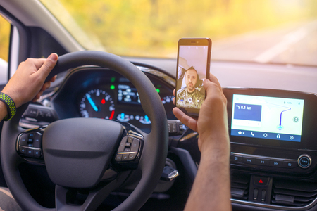 Photo pour Male driver using smartphone to capture selfie pictures while driving - image libre de droit