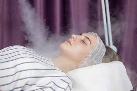 Foto de Beauty treatment of young female face, ozone facial steamer - Imagen libre de derechos