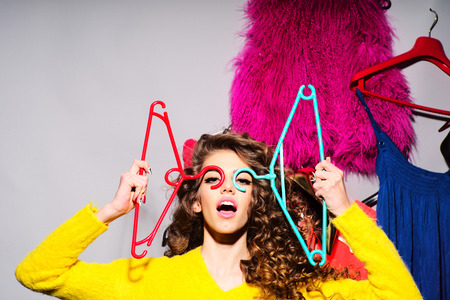 Photo pour Crazy young girl with curly hair in yellow sweater holding hangers standing amid colorful clothes pink red blue colors on grey wall background, horizontal picture - image libre de droit