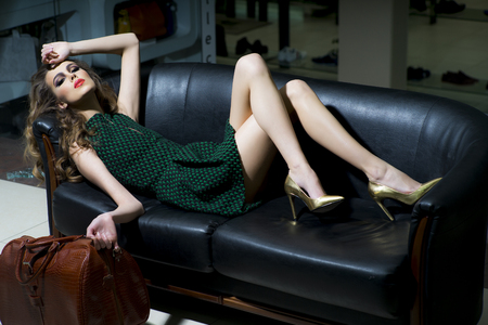 Foto de Sensual slender young blonde woman in green dress and gold shoes with brown bag lying on black leather sofa, horizontal picture - Imagen libre de derechos