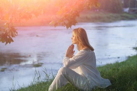 Photo pour Misterious young woman in white clothes sitting on river bank in calm on natural sunset background, horizontal picture - image libre de droit