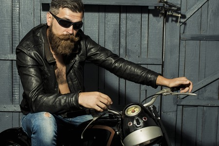 Photo for Handsome brutal unshaven male biker with long beard in brown leather jacket jeans and sun glasses sitting in garage on motorcycle looking forward on grey wooden background, horizontal picture - Royalty Free Image