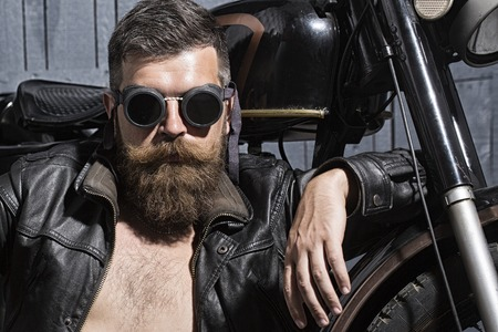 Photo pour Portrait of serious confident handsome sexy unshaven man with beard and handlebar moustache in leather biker jacket with bare torso and aviator sunglasses sitting near motorcycle, horizontal picture - image libre de droit