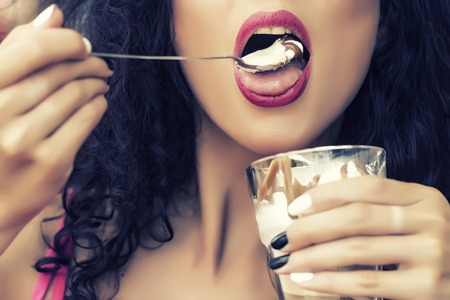 Closeup of sexual attractive female face of brunette lady with curly hair and open mouth eating cold dessert of ice cream and coffe glissade from glass with spoon, horizontal picture