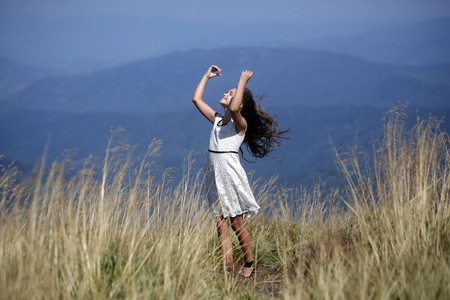 Small attractive happy brunette girl in white lace summer dress standing in mountain valley with deep dry spikelet grass htouching hair isunny day outdoor on natural blue background, horizontal picture