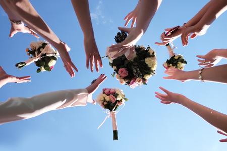 Photo pour Women's hands trying catch four beautiful brides bouquets of roses pastel colors on clear blue sky background, horizontal photo - image libre de droit