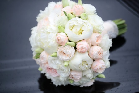Photo pour Beautiful fresh soft wedding decorative round shape bouquet of pink rose white peony and green flowers lying on black glossy background outdoor, horizontal picture - image libre de droit