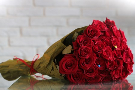 Photo pour Closeup of one big beautiful colorful soft aroma fresh wedding or birthday bouquet of many red rose flowers lying sunny day outdoor on natural background, horizontal picture - image libre de droit