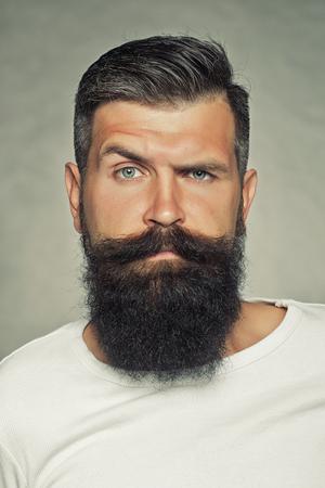 Foto de Portrait closeup of one handsome sensual grey-haired unshaven man with long beard moustache and eyebrow raised model looking forward in studio on light background, vertical picture - Imagen libre de derechos