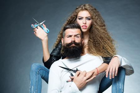 Photo for Couple of long-haired young beautiful woman holding two pairs of scissors sitting behind handsome bearded grey-haired man with moustache both looking forward on grey background, horizontal picture - Royalty Free Image