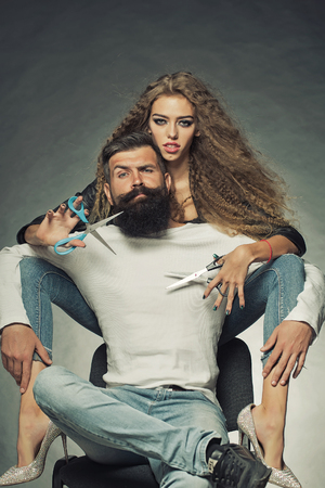Photo pour Couple of long-haired young beautiful woman holding two pairs of scissors sitting behind handsome bearded grey-haired man with moustache both looking forward on grey background, vertical picture - image libre de droit
