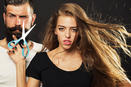 Photo pour Closeup view of young beautiful couple of beautiful fashionable female barber cutting and holding scissors and handsome man with long beard in studio on black background, horizontal picture - image libre de droit