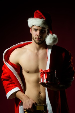 Foto de Closeup portrait of one handsome sexy new year young muscular man with bare chest in red christmas santa claus winter coat with hood holding present box on pink studio background, vertical picture - Imagen libre de derechos