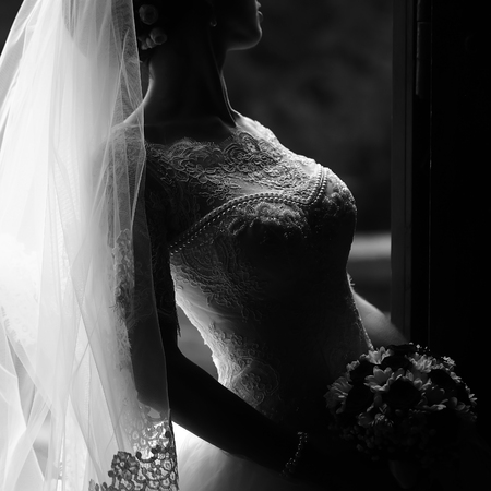 Photo pour Photo closeup of beautiful young bride in ornamental wedding lace dress long veil holding elegant bouquet of fresh flowers for bridal ceremony black and white on grey background, square picture - image libre de droit