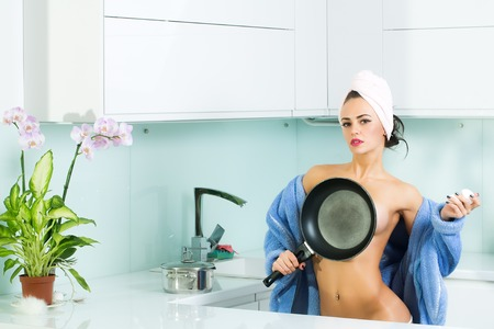 One sexy pretty sensual female housewife in open blue terry dressing gown and towel turban on head covering bare chest and body with frying pan standing in kitchen in morning life, horizontal picture