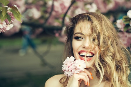 Beautiful young woman with long curly hair and bare shoulders and happy smiling face in spring pink flowers bloom