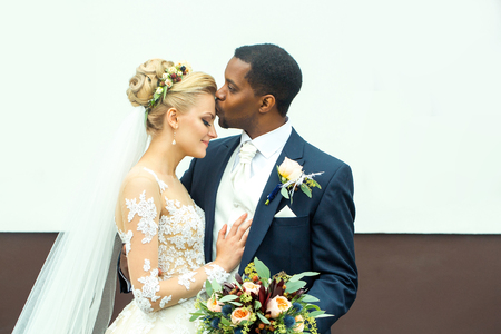 Photo for Young man elegant african American groom kisses tenderly beautiful woman happy bride in white dress and veil married couple on wedding day - Royalty Free Image