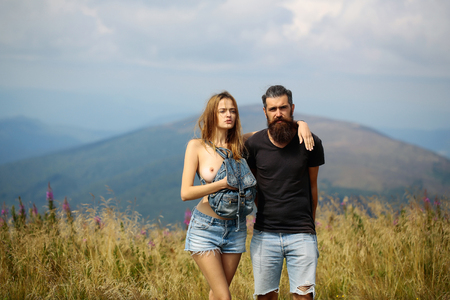 Photo pour Romantic couple of pretty naked girl with bare chest and handsome bearded man in love embrace on cliff on summer day over mountain tops and sky - image libre de droit