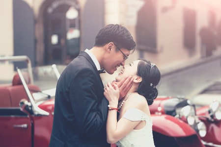 Photo for Chinese cute bride and groom young newlyweds just married couple kiss on streets of old city on wedding day in long white wedding dress stands outdoors near red retro car - Royalty Free Image
