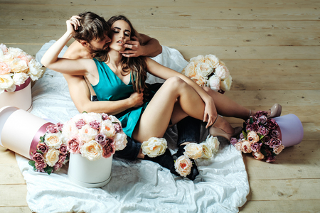 Photo pour Sexy couple young beautiful cute lovers in love pretty girl and sexi man with boxes of flowers hug on wooden floor - image libre de droit