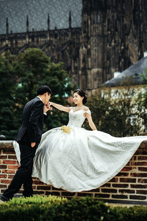 Photo for Chinese cute bride and groom young newlyweds just married happy couple kiss on streets of old city on wedding day - Royalty Free Image