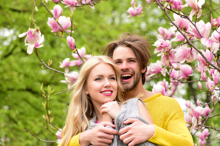 Photo for romantic moment of beautiful newlywed couple in spring garden under blossoming magnolia tree branches and green grass, happy couple in love - Royalty Free Image