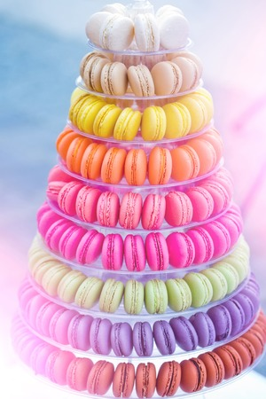 Photo pour Colorful french macarons, multilevel cake pyramid, on plastic, dessert stand or plate on blurred background. Food, dieting. Birthday, anniversary, wedding celebration - image libre de droit