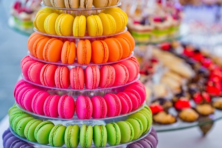 Photo pour macaron. Delicious french macarons, colorful, multilevel pyramid, and sweet cake dessert on plates or stands on blurred background. Food, dieting. Birthday, anniversary, wedding celebration - image libre de droit
