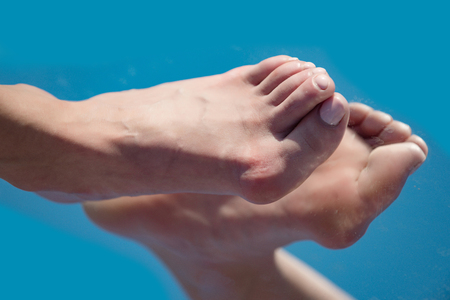 Photo pour foot step. big bone on toe with pedicure reflecting in mirror on blue background, medicine and health, relax and tiredness, age and evolution, future and success - image libre de droit