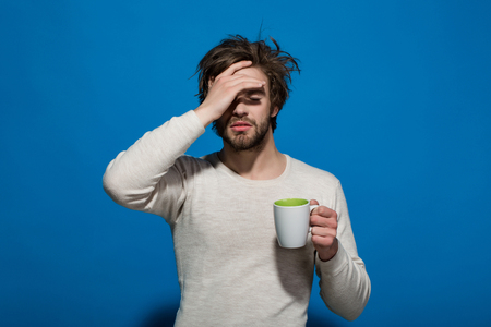 Photo pour morning. sleepy tired man with headache hold cup of tea or coffee has uncombed hair in underwear on blue background, morning refreshment and drink - image libre de droit