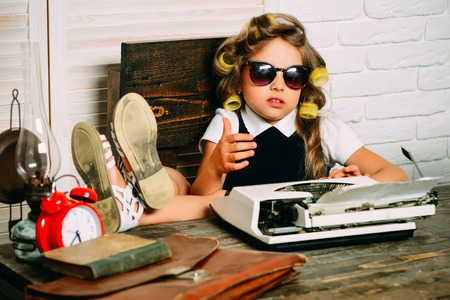 Foto de Little baby secretary. Kid choose career in glasses. Small girl with curler in hair. Education and childhood. Child with briefcase and alarm clock. - Imagen libre de derechos