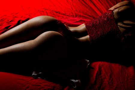 Photo pour Sexy woman laying on red bed. Beauty and fashion. Buttocks of girl in lingerie. Woman in erotic underwear pants. - image libre de droit