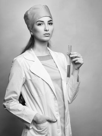 Foto de Scientist female doctor in medical uniform with flask of chemical laboratory in studio on orange background - Imagen libre de derechos