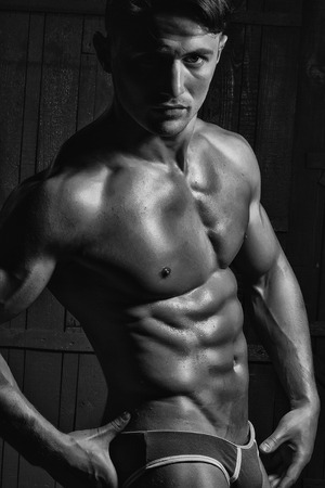 Photo for Handsome athletic sexual young guy bodybuilder brunet with strong muscular torso perfect cool six-pack abdominal muscles wearing fashion underwear looking straight posing on dark background closeup - Royalty Free Image