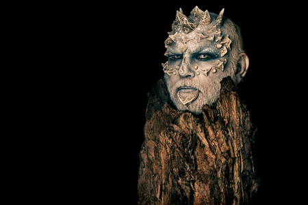 Photo for Tree spirit and fantasy concept. Monster with sharp thorns and warts. Druid behind old bark isolated on black. Goblin with horns on head. Man with dragon skin and bearded face, copy space - Royalty Free Image