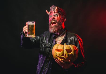 Foto de Halloween holiday celebration and party. Man with satan horns hold pumpkin. Devil smile with glass mug. Hipster demon drink beer on black background. Bad habits and addiction concept. - Imagen libre de derechos
