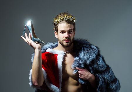 Photo pour Drag queen, homosexual and trans. Freak, gay and transvestite. Cinderella prince with shoe on grey background. Freedom and lgbt, kitsch. Christmas guy in santa fur coat in crown. - image libre de droit