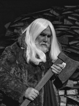 Foto de Old man druid with long silver hair and beard in fur coat stands with axe on woodpile background - Imagen libre de derechos