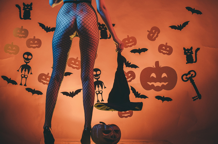 Foto de Halloween Holiday. Halloween sexy female legs in fishnet tights and shoes. Legs of girl on skeleton and bat background. party and celebration. buttocks of woman at pumpkin hold witch hat. - Imagen libre de derechos